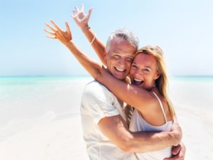 Portrait of excited mature woman in her husbands arms at the beach
